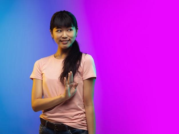 Saudações. retrato de mulher jovem asiática isolado em fundo de estúdio gradiente em néon. bela modelo feminino em estilo casual. conceito de emoções humanas, expressão facial, juventude, vendas, anúncio. folheto