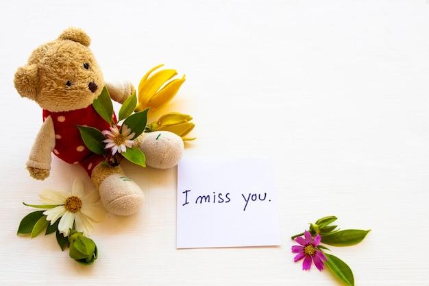 Saudades da sua mensagem escrita à mão com flores ursinho de pelúcia