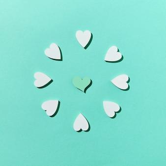 Saudando a composição do feriado festivo de corações de gesso artesanais em uma parede turquesa pastel com sombras duras, copie o espaço. vista do topo. dia dos namorados