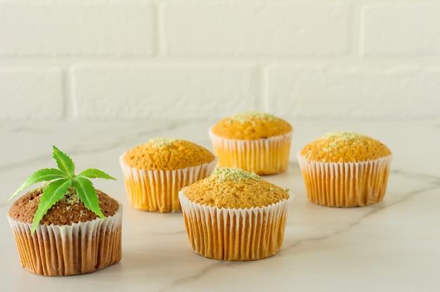 Saudáveis e saborosos muffins sem glúten e veganos cobertos com sementes de cânhamo em uma mesa de mármore. queques de bolinho de maconha com folhas de cannabis.