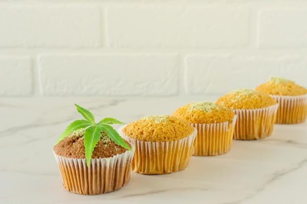 Saudáveis e saborosos muffins sem glúten e veganos em uma fileira cobertos com sementes de cânhamo em uma mesa de mármore. queques de bolinho de maconha com folhas de cannabis.