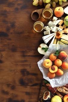Saudáveis frutas e queijo no fundo de madeira, vista superior