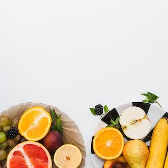 Saudáveis frutas frescas na tigela e placas em fundo branco