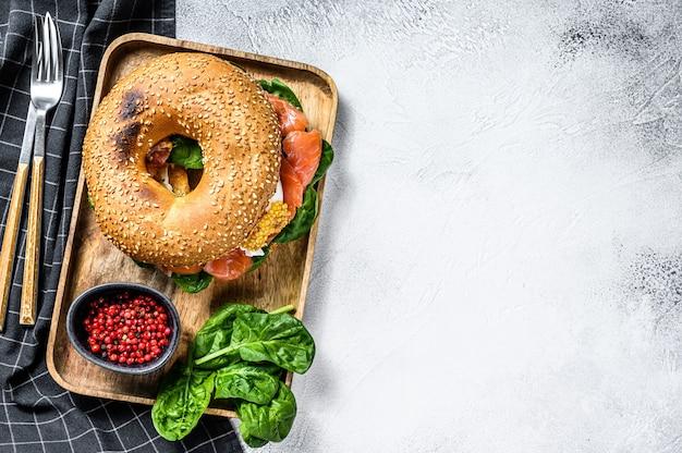 Saudável bagel recém cozido assado com salmão defumado, espinafre e ovo.