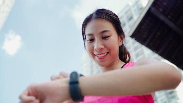 Saudável, bonito, jovem, asiático, atleta, mulher, armando, e, verificar, progresso, olhar, monitor freqüência cardíaca