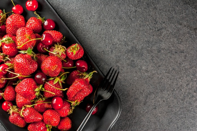 Saudável café da manhã, almoço ou lanche. frutas e bagas de verão. cerejas frescas orgânicas e morangos em um prato retangular, com um garfo, em uma mesa de pedra preta. vista do topo
