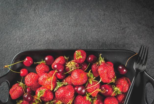 Saudável café da manhã, almoço ou lanche. frutas e bagas de verão. prato retangular orgânico de cerejas e morangos, com um garfo, em uma mesa de pedra preta.