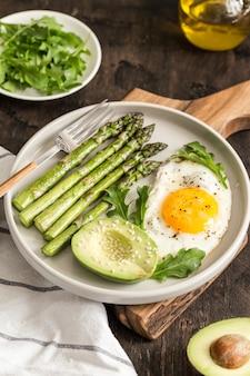 Saudável café da manhã caseiro com aspargos, ovo frito, abacate e rúcula. conceito de alimentação saudável de quarentena. dieta ceto