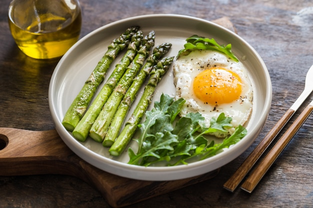 Saudável café da manhã caseiro com aspargos, ovo frito e rúcula. conceito de alimentação saudável de quarentena. dieta ceto