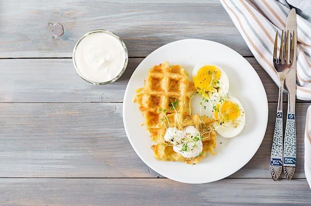 Saudável café da manhã ou lanche. waffles de batata e ovo cozido na mesa de madeira cinza. vista do topo. configuração plana