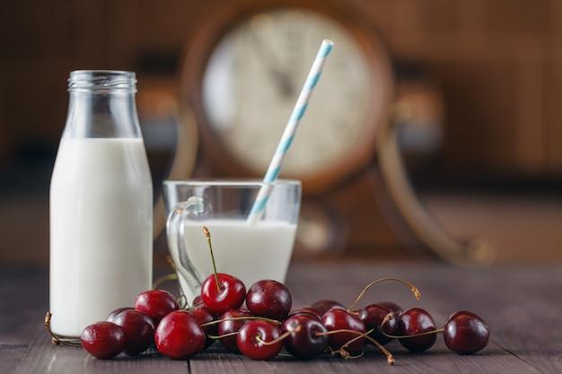 Saudável de café da manhã de cereja, copo de leite sobre fundo de madeira