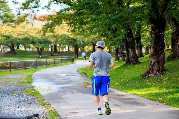 Saudável do homem do esporte asiático que movimenta-se no parque. conceito de relaxamento.