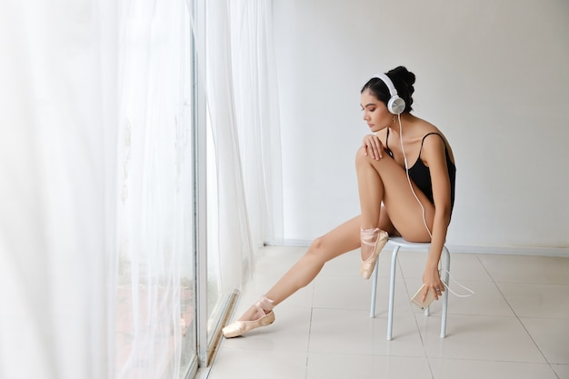 Saudável e desportiva mulher asiática nova bonita no sportswear preto sentado com fone de ouvido, ouvindo música do telefone celular enquanto treinava a dança de balé na parede branca. tecnologia e conceito saudável