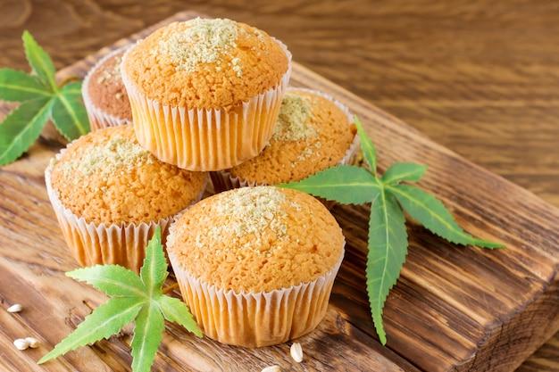 Saudável e saboroso vegan e muffins sem glúten cobertos com sementes de cânhamo em um close-up de mesa de madeira. queques de bolinho de maconha com folhas de cannabis.