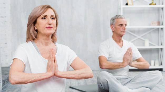 Saudável, par velho, sentando, em, loto, pose, com, orando, mãos