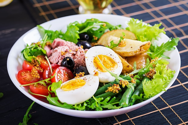 Saudável salada saudável de atum, feijão verde, tomates, ovos, batatas, close-up de azeitonas pretas em uma tigela em cima da mesa.