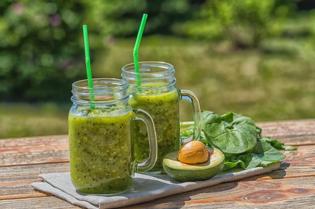 Saudável vegan green smoothie com espinafre em potes de vidro e abacate, ao ar livre, sobre o fundo da natureza.