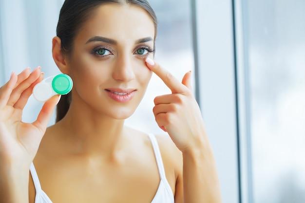 Saúde. a rapariga prende a lente de contato nas mãos. retrato de uma mulher bonita com olhos verdes e lentes de contato.