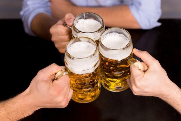 Saúde! close-up de pessoas segurando canecas com cerveja