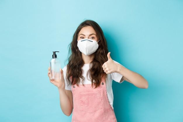 Saúde, coronavírus e conceito de distanciamento social. mulher jovem com máscara facial, usando respirador e mostrando desinfetante para as mãos com o polegar para cima, recomendando anti-séptico, fundo azul.