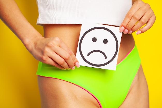 Saúde da mulher, corpo feminino segurando o cartão de sorriso triste perto do estômago.