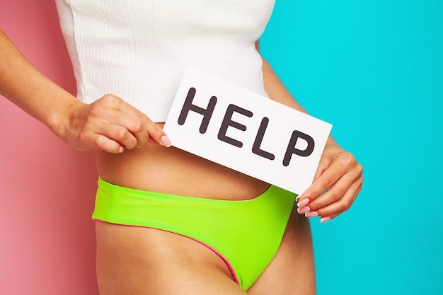 Saúde da mulher. corpo feminino segurando um símbolo de cartão de ajuda perto do estômago.