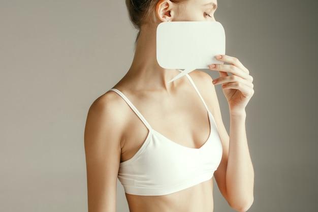 Saúde da mulher. modelo feminino segurando um cartão vazio perto da mama. jovem adulta com papel para sinal ou símbolo isolado na parede cinza. corte parte do corpo. problema e solução médicos.