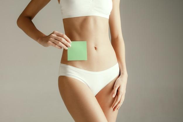 Saúde da mulher. modelo feminino segurando um cartão vazio perto do estômago. jovem adulta com papel para sinal ou símbolo isolado na parede cinza. corte parte do corpo. problema e solução médicos.