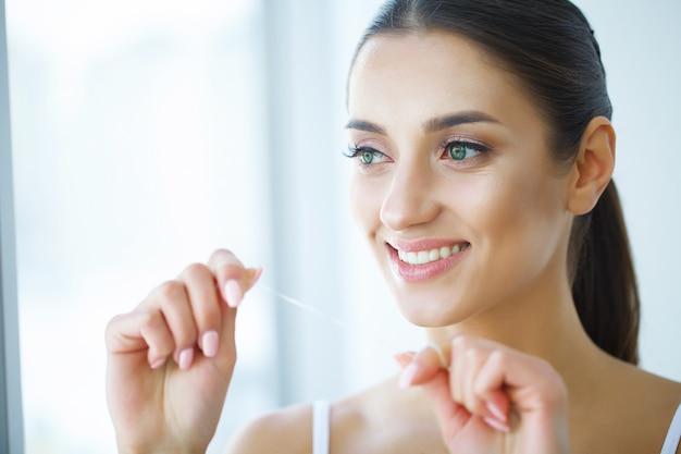 Saúde dental. mulher com sorriso bonito flossing dentes saudáveis. imagem