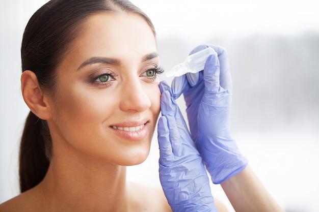 Saúde e beleza. cuidado do olho jovem mulher bonita que guarda gotas para os olhos. boa visão. garota feliz com olhar fresco