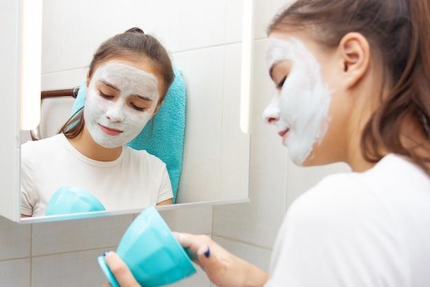 Saúde e beleza. cuidados com a pele facial. jovem faz uma máscara facial de limpeza hidratante