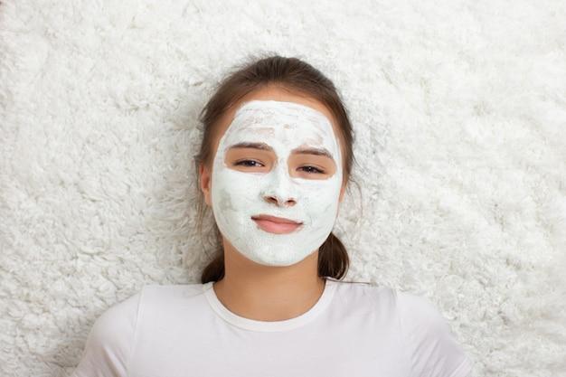 Saúde e beleza. cuidados com a pele facial. uma jovem garota com uma máscara hidratante no rosto encontra-se com um smartphone