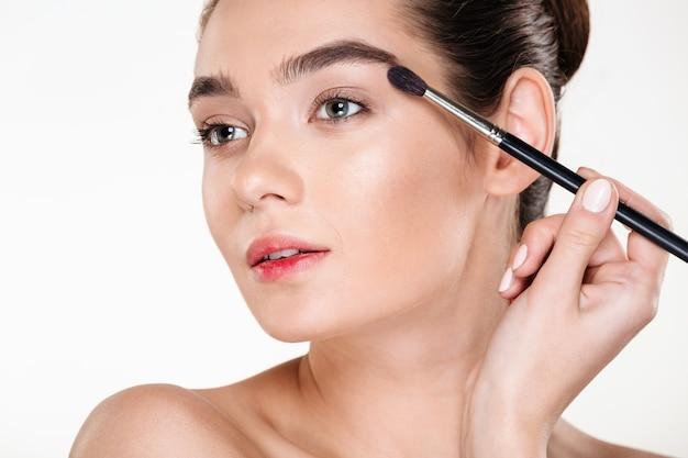 Saúde e beleza da mulher glamour na moda, com cabelos escuros no coque, aplicar sombra para os olhos usando o pincel