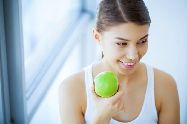 Saúde e beleza. moça bonita com os dentes brancos que guardam as mãos da maçã verde fresca. uma mulher com um sorriso bonito. saúde dentária