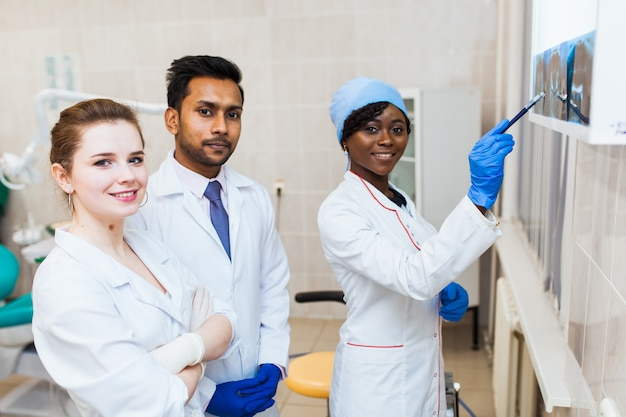 Saúde e cuidados de saúde. um grupo multinacional de dentistas examina radiografias na presença de um paciente. pratique em uma universidade médica.