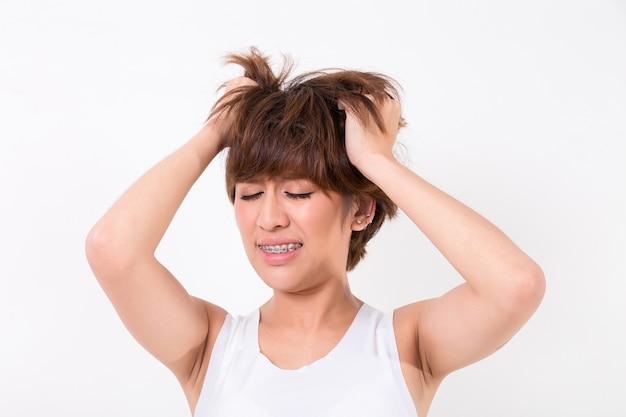Saúde e dor. mulher nova esgotada forçada que tem a dor de cabeça de tensão forte. isolado no branco b