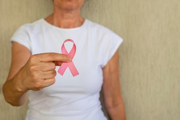 Saúde feminina outubro rosa mulher com laço rosa na mão campanha de prevenção do câncer de mama