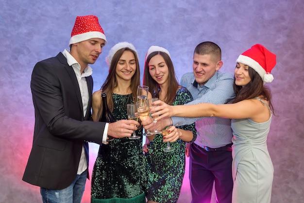 Saúde! grupo de amigos comemora e levanta taças de champanhe para o brinde, ano novo de 2020