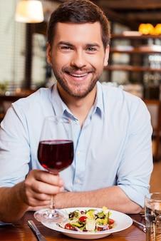 Saúde! jovem bonito brindando com vinho tinto e sorrindo enquanto está sentado no restaurante