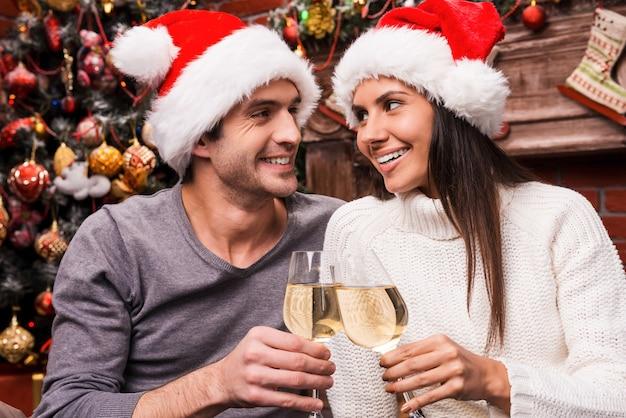 Saúde! jovem casal feliz com chapéu de papai noel, abraçando-se e comemorando com vinho e com a árvore de natal ao fundo