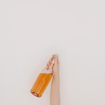 Saúde! mão de uma mulher segurando uma garrafa de champanhe rosa contra uma parede branca
