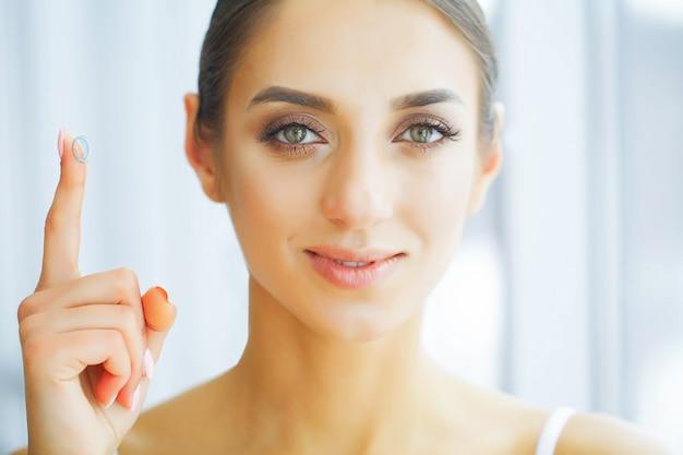 Saúde. mulher feliz com lentes de contato no dedo. cuidado do olho