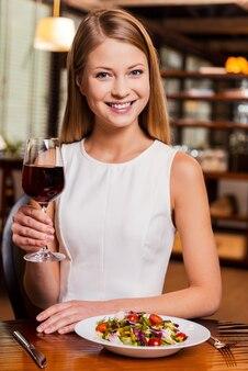 Saúde! mulher jovem e bonita brindando com vinho tinto e sorrindo enquanto está sentada no restaurante