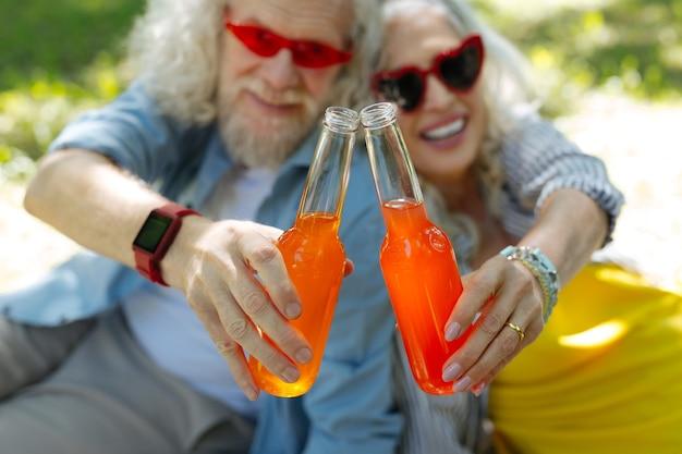 Saúde para nós. foco seletivo de garrafas com bebida sendo batida