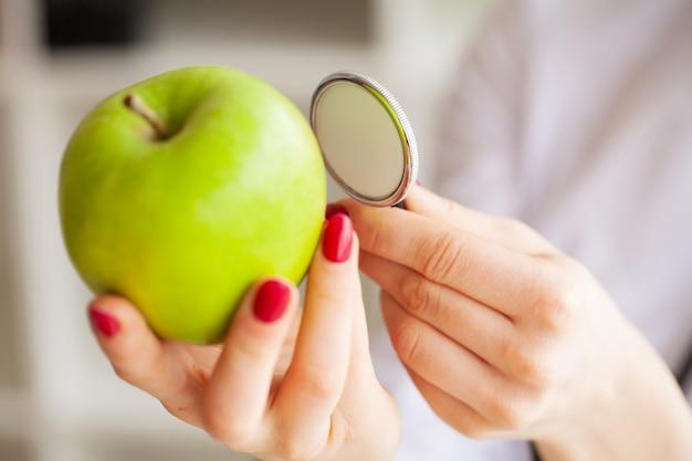 Saúde. retrato da nutricionista sorte na sala de luz. segura a maçã verde e a fita de centímetro. nutrição saudável. legumes frescos e frutas na mesa