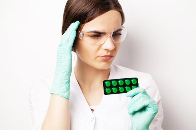 Saúde sexual, um médico de jaleco branco segurando uma pílula para uma vida sexual saudável dos homens.