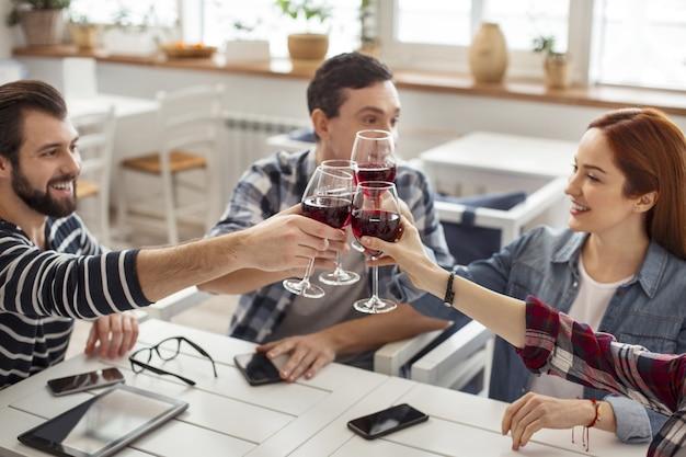 Saúde. velhos melhores amigos alegres e bonitos sentados à mesa, bebendo vinho e conversando