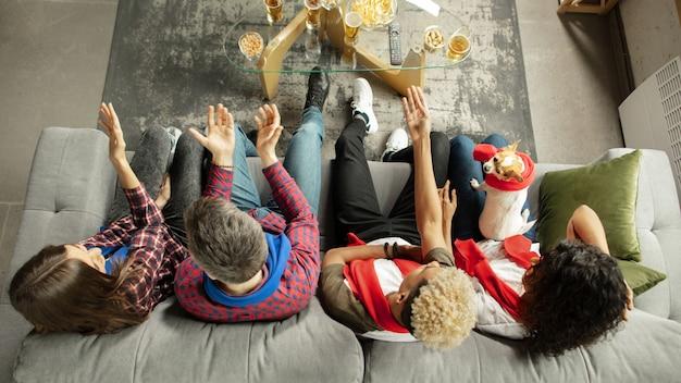 Saúde, vista de cima. pessoas empolgadas assistindo jogo esportivo, campeonato em casa. amigos multiétnicos, fãs torcendo pelo time favorito