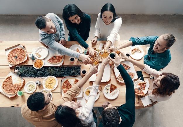 Saúde! vista superior de jovens em trajes casuais brindando uns aos outros e sorrindo durante um jantar dentro de casa