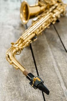Saxofone dourado bonito no fundo de madeira